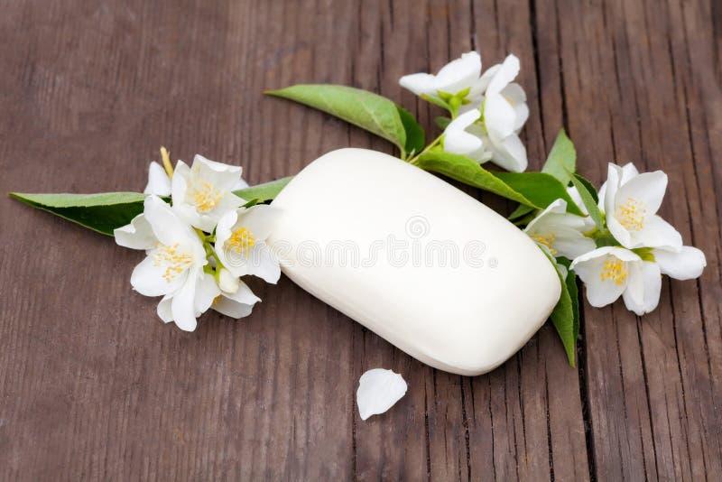 Flores y jabón del jazmín en una tabla de madera vieja fotografía de archivo libre de regalías