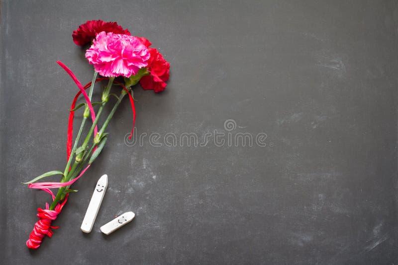 Flores y pizarra en concepto del fondo del día del profesor de la sala de clase foto de archivo libre de regalías