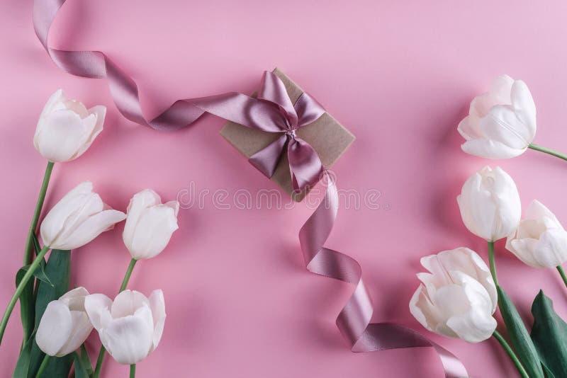 Flores y regalo blancos de los tulipanes sobre fondo rosa claro Greeti foto de archivo