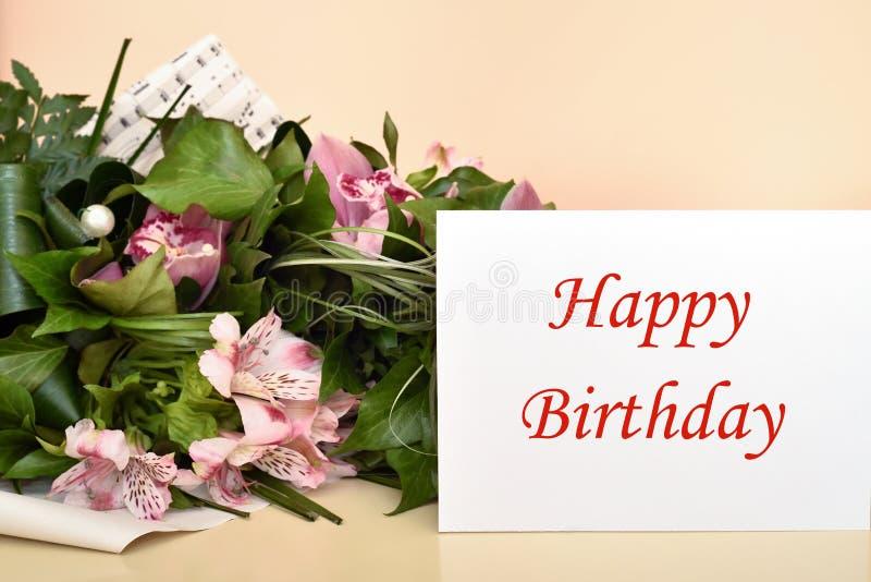 Flores y tarjeta de felicitación con el mensaje del feliz cumpleaños fotos de archivo