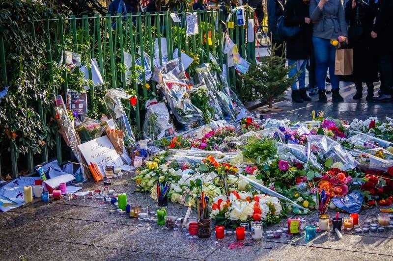 Flores y velas en memoria de las víctimas de los attentados terroristas de Charlie en París en Francia imagen de archivo libre de regalías