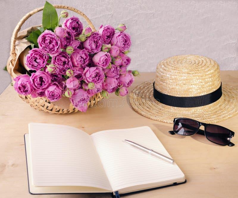 Floresce as rosas, livro para entradas, chapéu de palha e vidros, em uma corte fotografia de stock royalty free