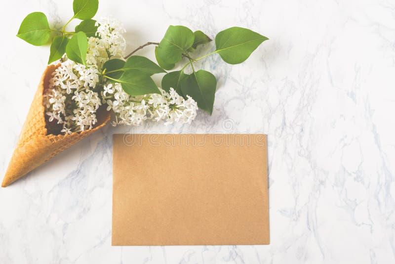 Floresce a composição Lilás no cone do waffle e envelope do ofício no fundo de mármore branco Configuração lisa, vista superior,  imagens de stock royalty free