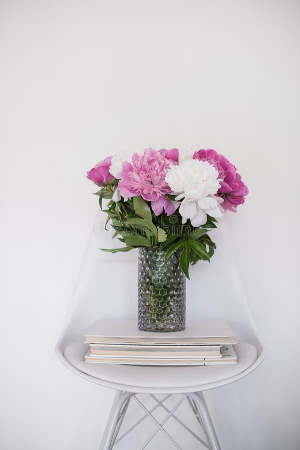 Floresce a decoração, peônias frescas na cadeira do desenhista na sala branca int imagens de stock