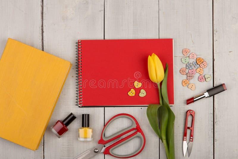 Florezca el tulipán, el cuaderno de notas rojo del espacio en blanco, el libro amarillo, las tijeras, el esmalte de uñas y los bo imagen de archivo libre de regalías
