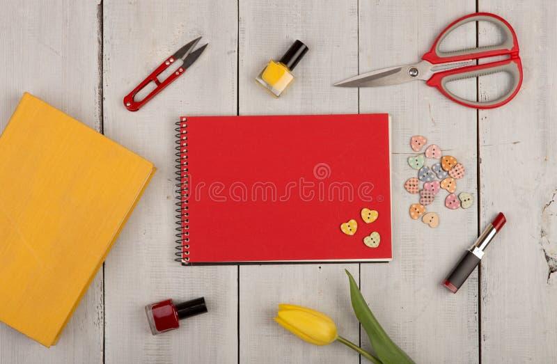 Florezca el tulipán, cuaderno de notas rojo del espacio en blanco, libro amarillo, tijeras, clavo po imagen de archivo libre de regalías