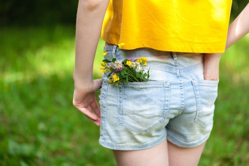 Florezca en un bolsillo grande de pantalones de los vaqueros, concepto del verano fotografía de archivo libre de regalías