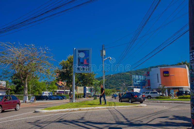FLORIANOPOLIS, BRAZIL - MAY 08, 2016: pedestrian crossing the street while some cars drive trough the street stock photography