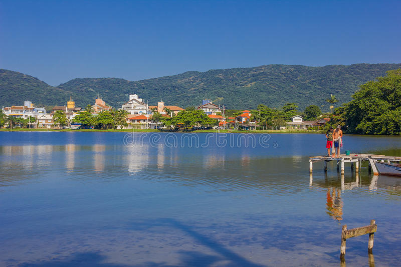 FLORIANOPOLIS, BRAZIL - MAY 08, 2016: two man standing over the dock with a fishing net, reflection of some houses on stock image