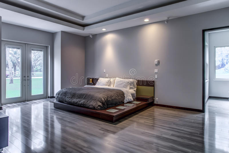 Florida luxury home modern minimalistic bedroom. Florida luxury home modern design bedroom with real wood floors and minimalistic design. View of front yard and stock image