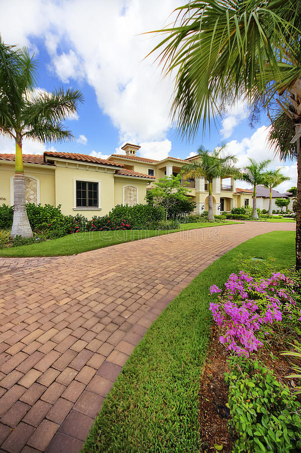 Florida luxury home with pillars. Florida luxury home in private community with front pillars, palm trees, landscaping, and paver block circular driveway stock photo