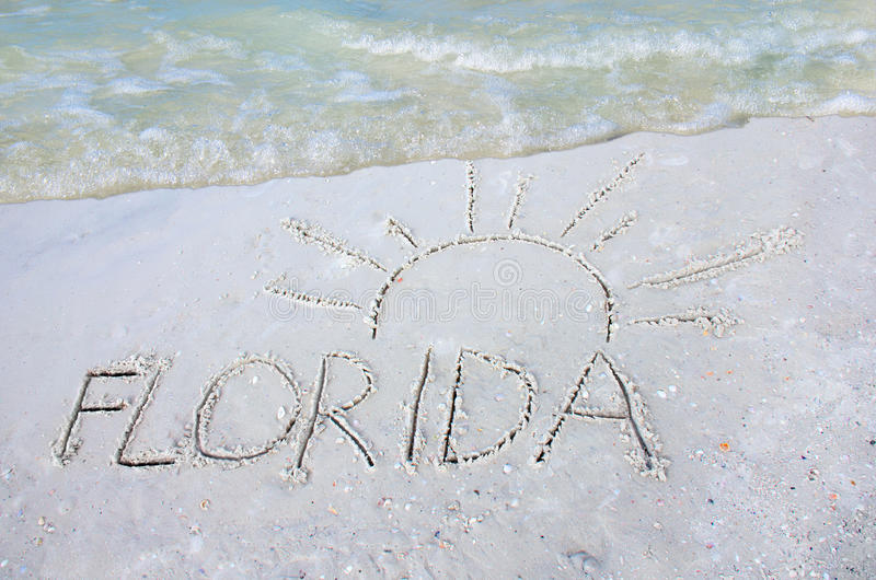 Florida och sol som dras i sand på stranden med en våg arkivbild