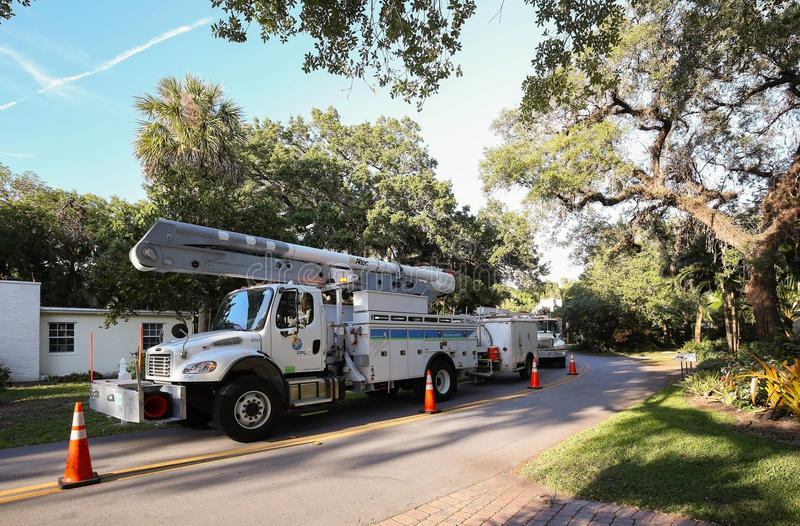 Florida Power and Light trucks parked on a residential street. FORT LAUDERDALE, FLORIDA, USA - April 9, 2016: A team of Florida Power and Light repair trucks royalty free stock photos