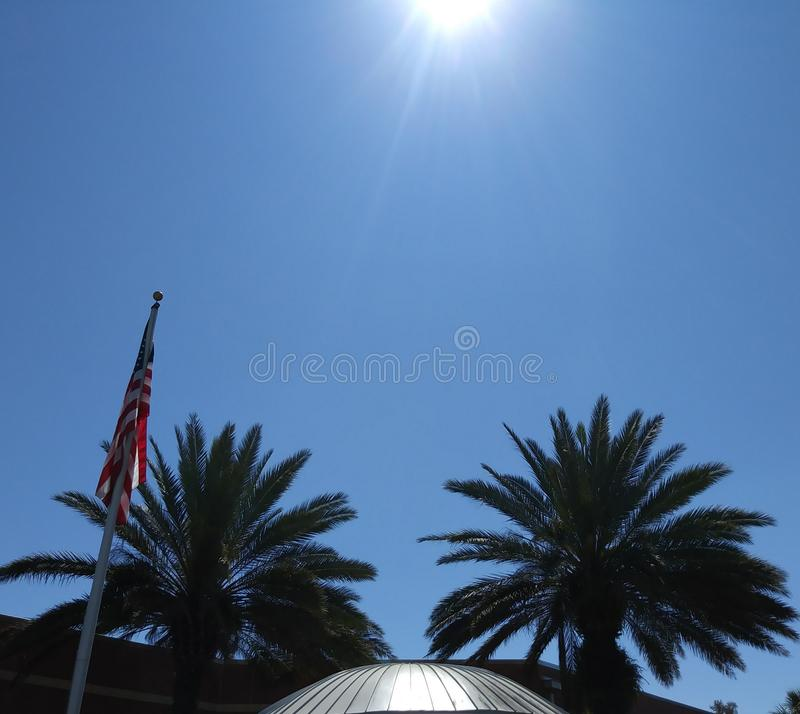 Florida sky, American Flag and Palm Trees. Early morning Florida sky, two palm trees, the American Flag and a silver dome royalty free stock image