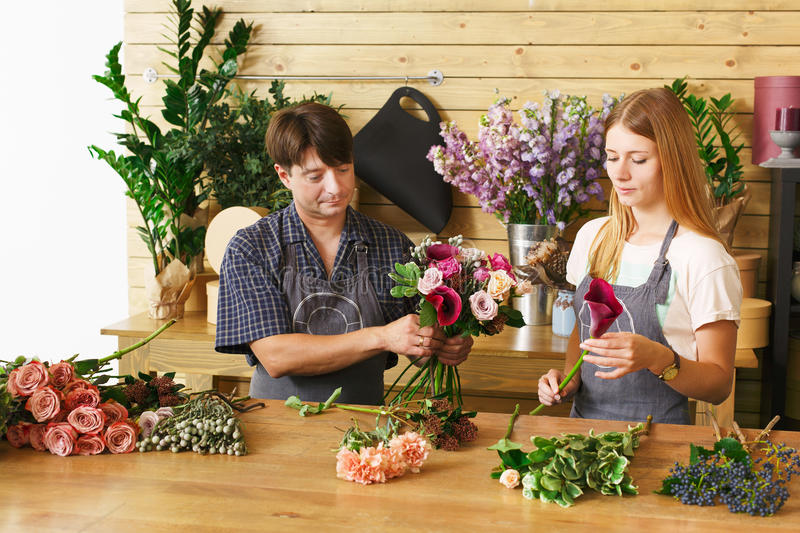 Florist and assistant in flower shop delivery make rose bouquet stock images