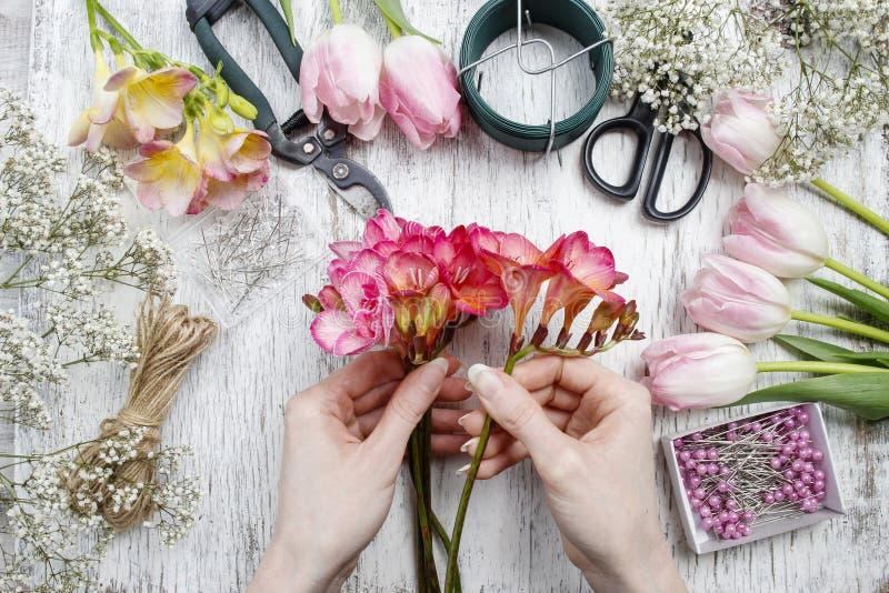 Florist bei der Arbeit Frau, die Blumenstrauß von den Frühlingsfreesieblumen macht lizenzfreie stockbilder