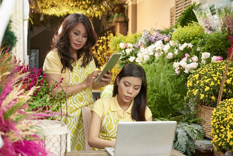 Florists accepting order. Florist chatting online with client when her coworker calculating price of order on digital tablet royalty free stock image