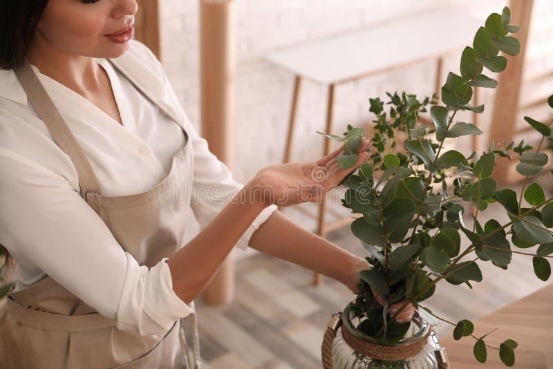 Florist con rami verdi al tavolo in laboratorio immagini stock libere da diritti