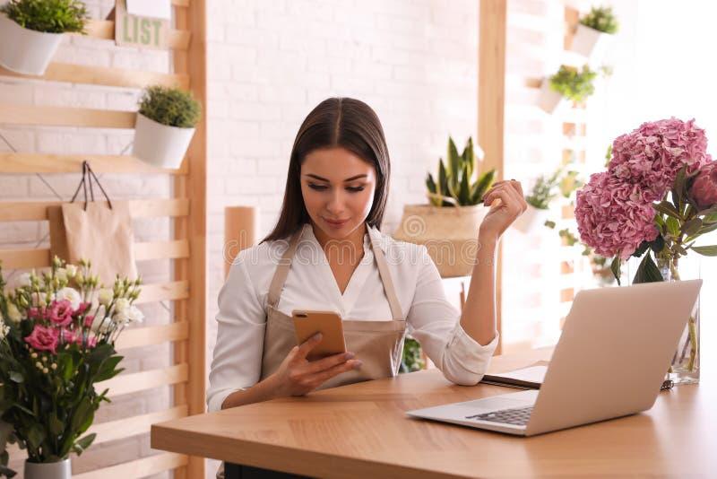 Florist con smartphone trabajando en laptop fotografía de archivo