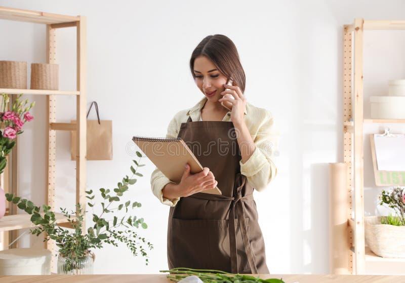 Florist con taccuino che parla di smartphone fotografie stock