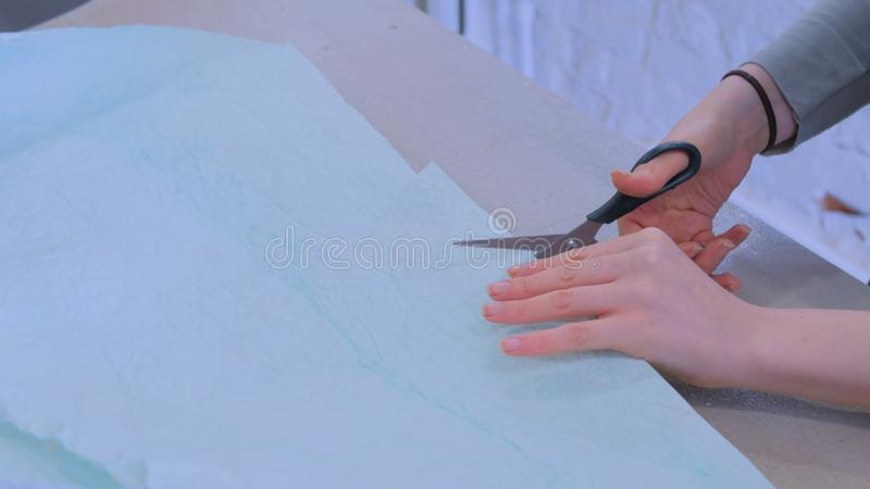 Florist cutting packing paper for bouquet at flower shop. Professional woman floral artist, florist cutting packing paper for bouquet at workshop, flower shop royalty free stock images