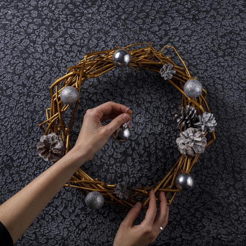 Florist decorator decorates a round wreath of dry branches. New Year`s decor. Top view royalty free stock photo