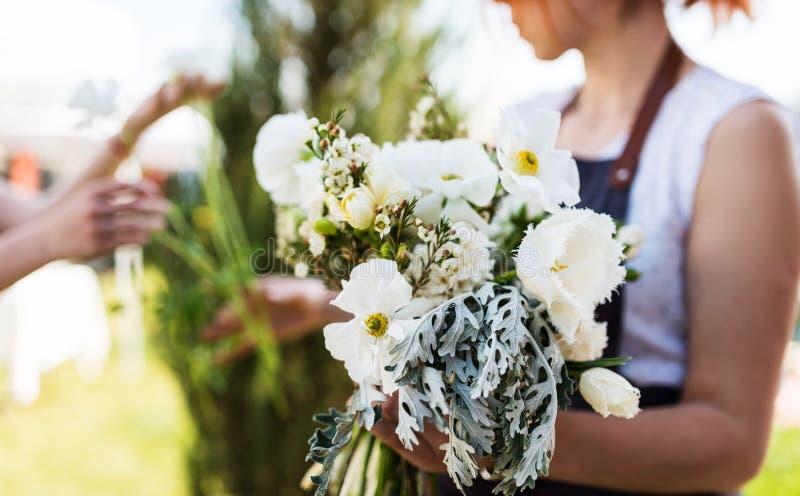Florist der jungen Frau, der einen Blumenstrauß mit weißen Blumen herstellt lizenzfreie stockbilder