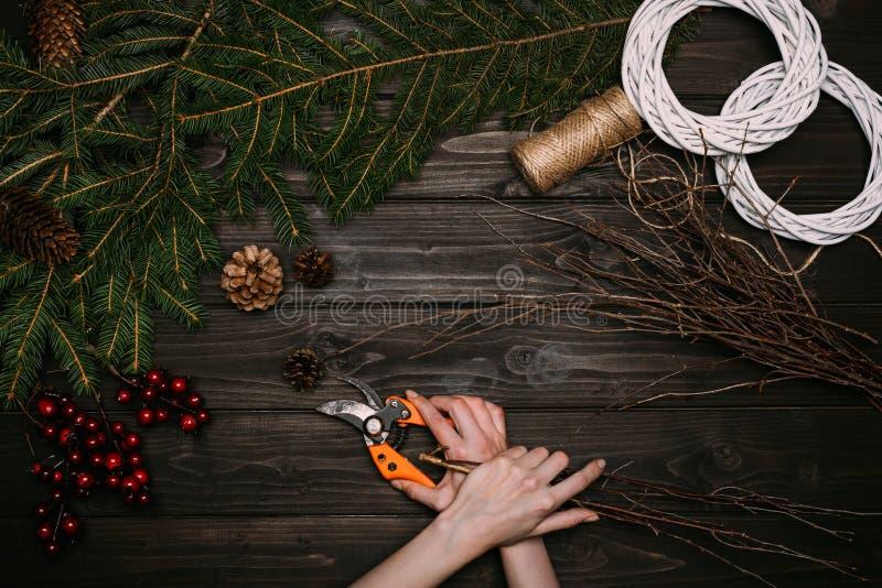 Florist, der Weihnachtskranz mit Niederlassungen macht lizenzfreie stockbilder