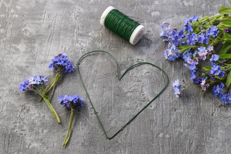 Florist en el trabajo: pasos para hacer que la puerta olvido-me-no se flor en forma de corazón fotos de archivo libres de regalías