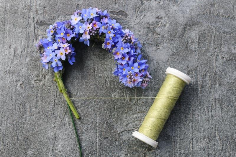 Florist en el trabajo: pasos para hacer que la puerta olvido-me-no se flor en forma de corazón fotografía de archivo libre de regalías