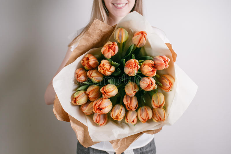 Florist girl with peony flowers or orange tulips Young woman flower bouquet for birthday mother's day. stock image