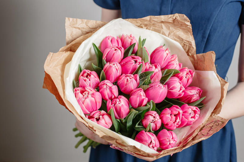 Florist girl with peony flowers or pink tulips Young woman flower bouquet for birthday mother's day. royalty free stock photos