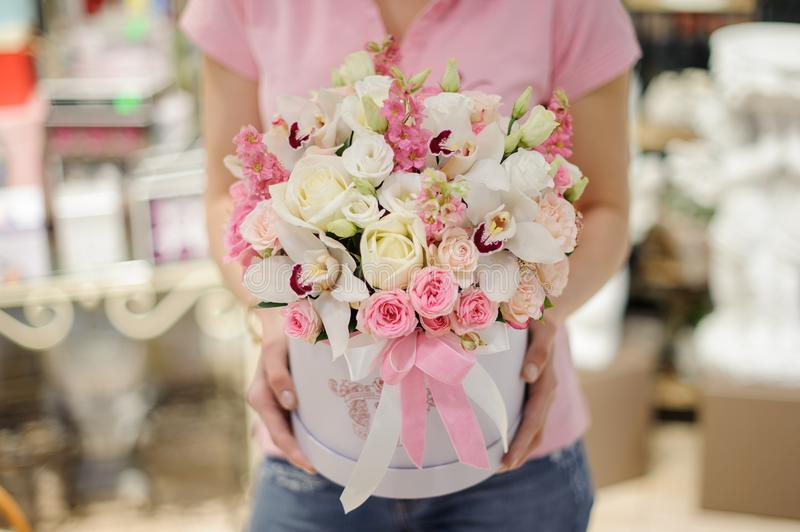 Florist holding a white flower box with flower composition in pink and white tones consisting of roses and other beautiful flowers. Florist holding a stylish stock photos
