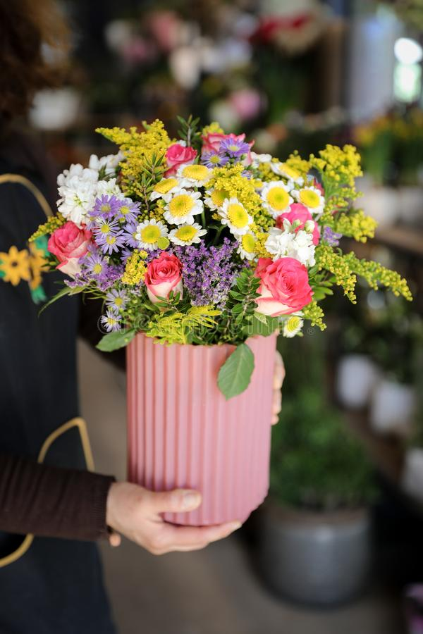 Florist holding a vase with beautiful flower arrangement of pink roses, lilac asters, white chrysanthemums and other plants in the royalty free stock image