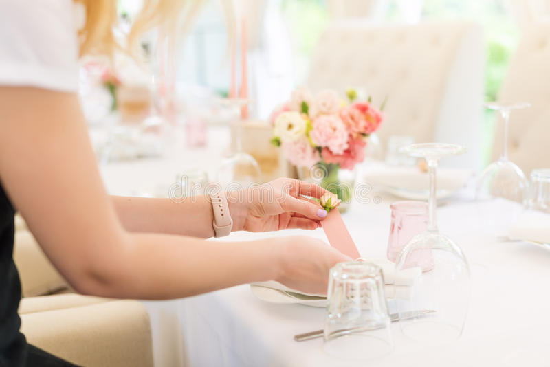 Florist preparing flower wedding decor in outdoor restaurant. No face, table set for holiday. stock image