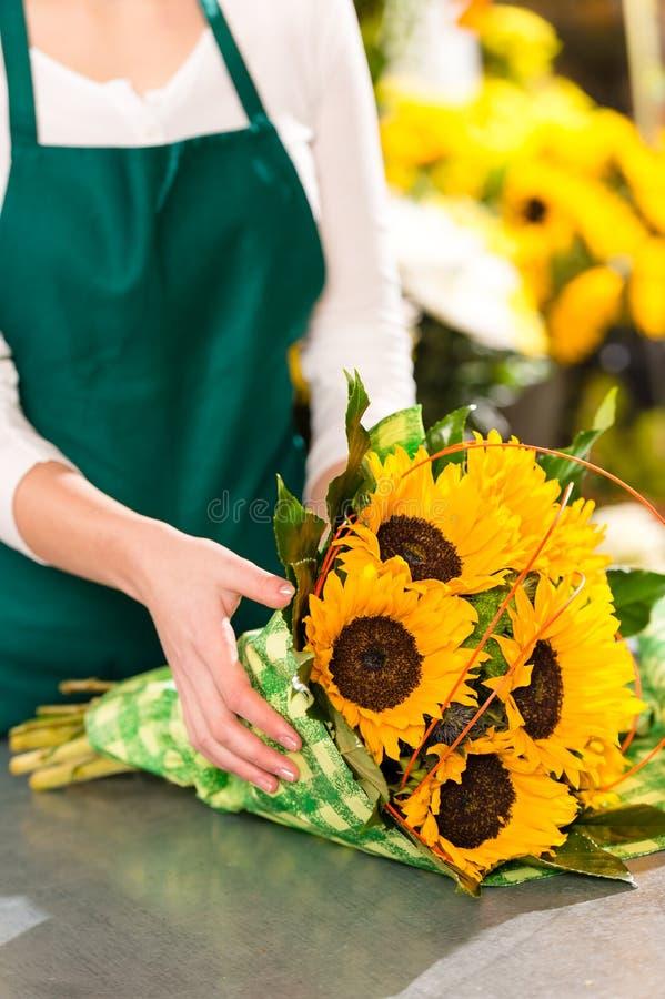Florist preparing sunflowers bouquet flower shop assistant stock photo