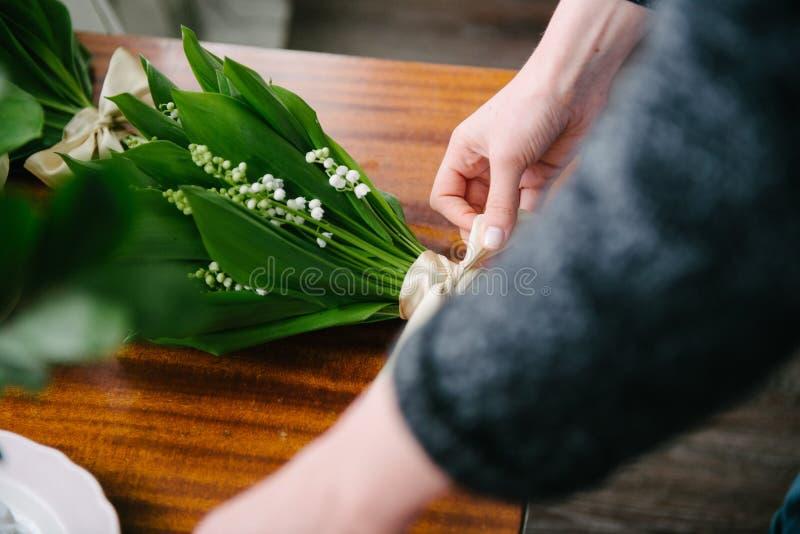 Florist& x27; s-tabell med blommor Blomsterhandlaren gör blommor fotografering för bildbyråer