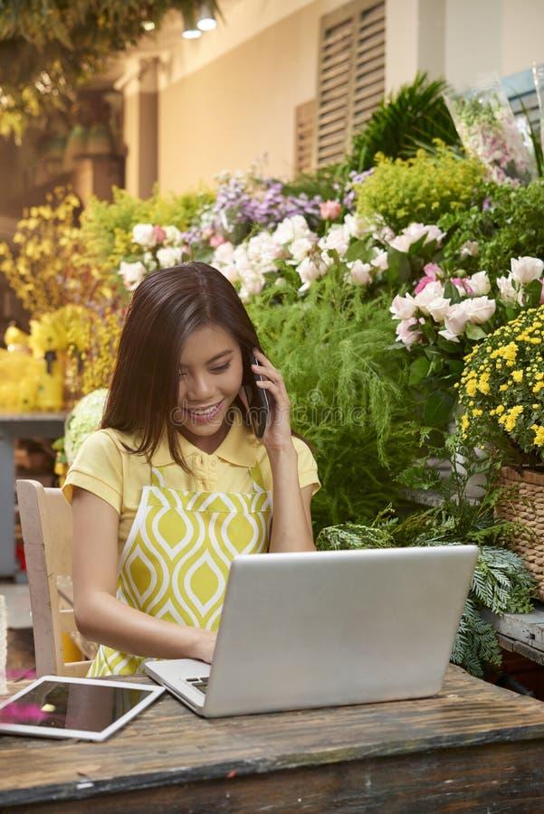Florist talking on phone royalty free stock photos