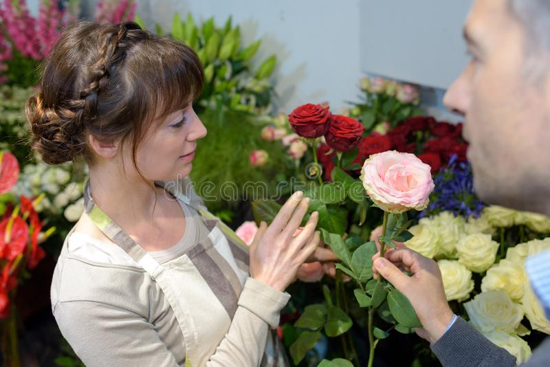 Florist talking to customer and giving advice stock photos