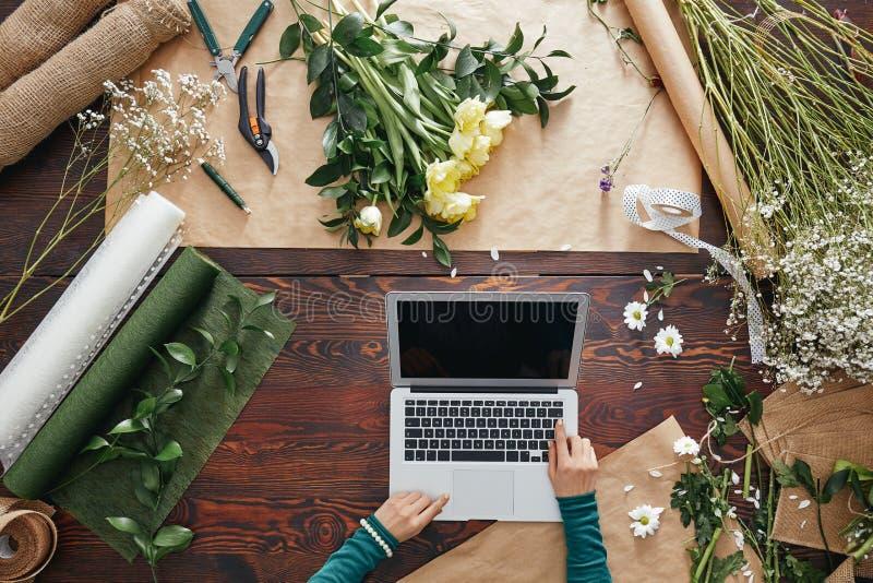 Florist using a laptop royalty free stock image