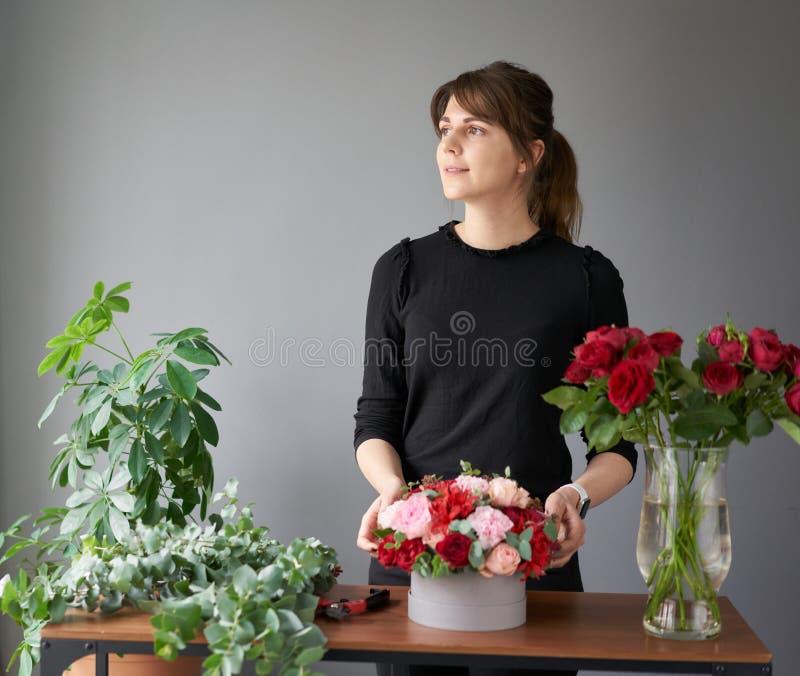 Florist woman creates flower arrangement in a round box. Beautiful bouquet of mixed flowers. Floral shop concept stock photo