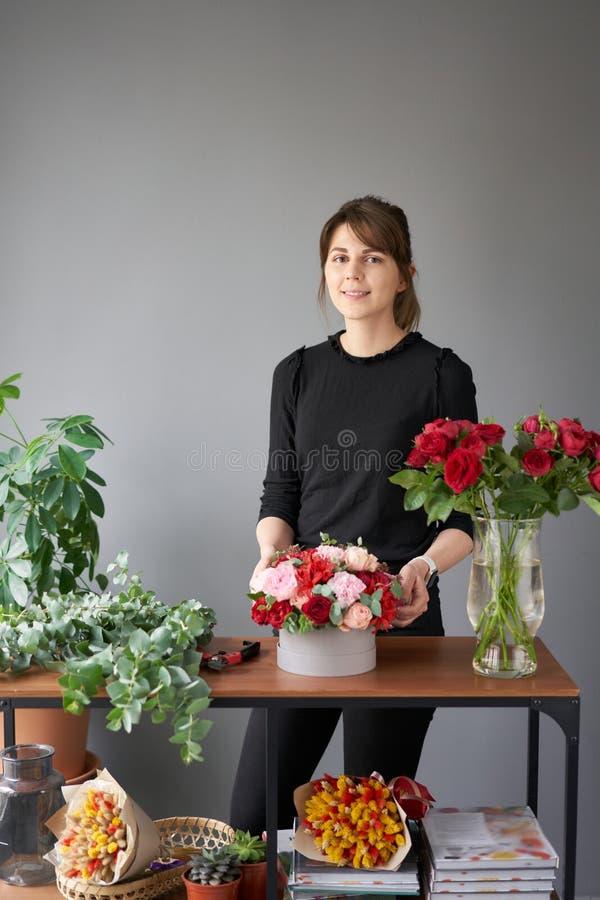 Florist woman creates flower arrangement in a round box. Beautiful bouquet of mixed flowers. Floral shop concept stock images
