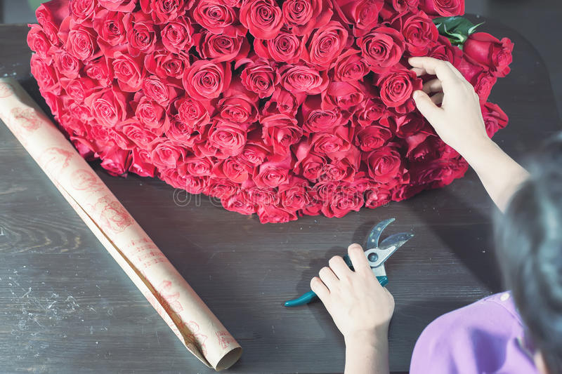Florist woman prepares a big bouquet of red roses. One hundred and one dutch rose. Florist flower shop. Holland. Wrapping paper. Concept holiday, birthday stock photo