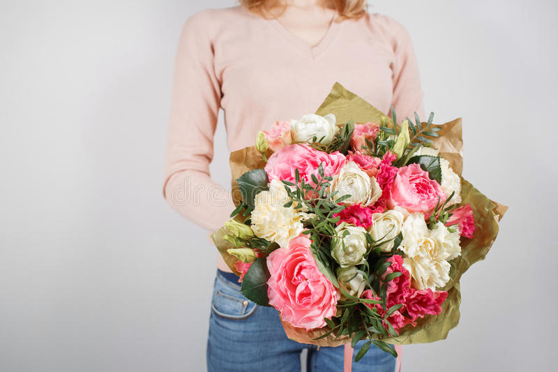 Florist at work. Make rich bouquet diferent color and flowers. Bunch in their hands.  stock image