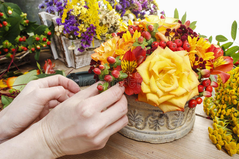 Florist At Work: Woman Making Bouquet Of Orange Roses And Autumn Stock Photo
