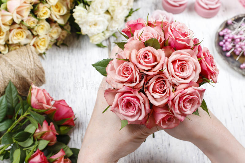 Florist at work. Woman making bouquet of pink roses royalty free stock image