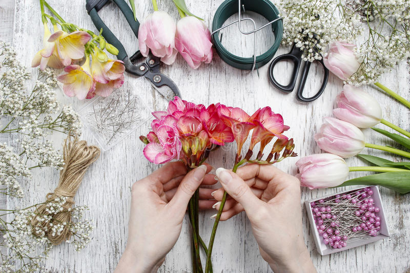 Florist at work. Woman making bouquet of spring freesia flowers. Party decoration royalty free stock images