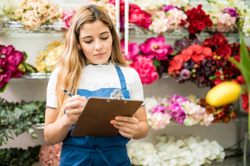 Florist working on a flower inventory royalty free stock photo