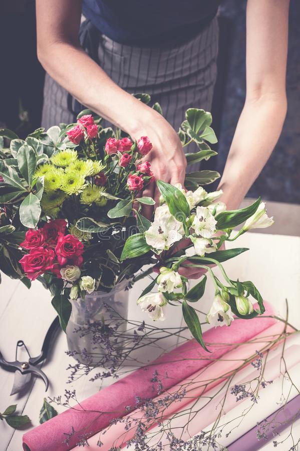 Florist works. Women`s hands making a wedding bouquet of roses. Small business concept. Vertical shot stock photos