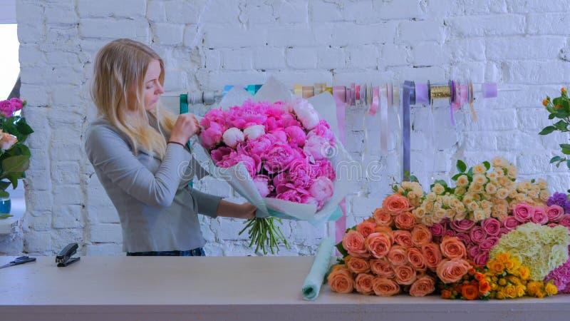 Florist wraps flowers in gift paper at flower shop. Professional woman floral artist, florist wraps flowers - pink peonies in gift paper at workshop, flower shop royalty free stock photo